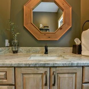 Bathroom - small craftsman medium tone wood floor and brown floor bathroom idea in Portland Maine with raised-panel cabinets, light wood cabinets, green walls and granite countertops