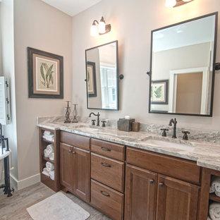 Exemple d'une salle de bain principale craftsman de taille moyenne avec un placard avec porte à panneau encastré, des portes de placard en bois sombre, une baignoire sur pieds, une douche d'angle, un WC à poser, un carrelage multicolore, du carrelage en ardoise, un mur gris, un sol en carrelage de céramique, un lavabo encastré, un plan de toilette en granite, un sol beige et une cabine de douche à porte battante.
