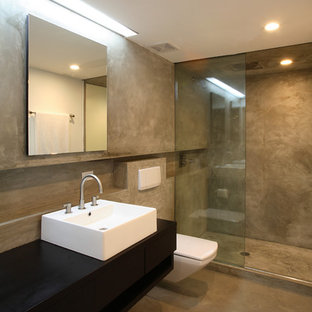 Photo of a large contemporary master bathroom in New York with a vessel sink, wood benchtops, a wall-mount toilet, concrete floors, black benchtops, an open shower, beige tile, cement tile, black walls, beige floor and an open shower.