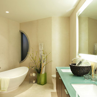 Réalisation d'une salle de bain design avec une baignoire indépendante, un plan de toilette en verre et un plan de toilette turquoise.