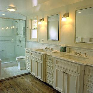 Idee per una stanza da bagno classica con lavabo sottopiano, ante con riquadro incassato, ante beige, doccia alcova e piastrelle bianche