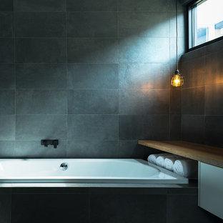メルボルンの中サイズのインダストリアルスタイルのおしゃれなマスターバスルーム (ベッセル式洗面器、フラットパネル扉のキャビネット、白いキャビネット、木製洗面台、ドロップイン型浴槽、黒いタイル、磁器タイル、黒い壁、ブラウンの洗面カウンター) の写真