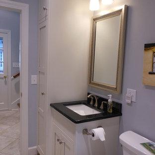 Foto di una piccola stanza da bagno con doccia tradizionale con lavabo sottopiano, ante a filo, ante bianche, top in granito, WC a due pezzi, pareti blu e pavimento alla veneziana