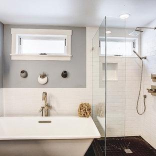 Modelo de cuarto de baño principal, contemporáneo, de tamaño medio, con armarios con paneles lisos, puertas de armario de madera en tonos medios, bañera exenta, ducha esquinera, sanitario de una pieza, baldosas y/o azulejos blancos, baldosas y/o azulejos de cemento, paredes grises, lavabo integrado, encimera de ónix, ducha con puerta con bisagras, suelo de pizarra, suelo gris y encimeras blancas
