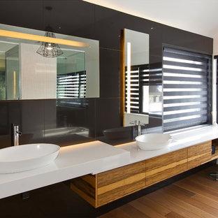 Ispirazione per una grande stanza da bagno padronale minimalista con ante lisce, ante in legno scuro, vasca freestanding, piastrelle nere, piastrelle in ceramica, pareti bianche, parquet chiaro, lavabo a bacinella, top in superficie solida e pavimento beige