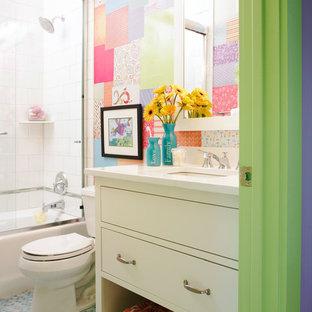 Idéer för att renovera ett mellanstort eklektiskt vit vitt badrum för barn, med vita skåp, släta luckor, ett badkar i en alkov, en dusch/badkar-kombination, en toalettstol med separat cisternkåpa, grå kakel, flerfärgad kakel, vit kakel, porslinskakel, flerfärgade väggar, ett undermonterad handfat, bänkskiva i akrylsten och mosaikgolv