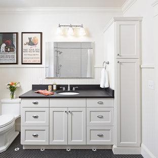 Idées déco pour une salle de bain classique avec un placard avec porte à panneau encastré, des portes de placard blanches, un mur blanc, un sol en carrelage de terre cuite, un lavabo encastré, un sol noir, un plan de toilette noir et boiseries.