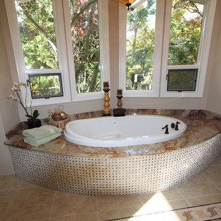 Immagine di una grande stanza da bagno padronale chic con lavabo a consolle, ante con bugna sagomata, ante in legno bruno, top in marmo, vasca idromassaggio, doccia ad angolo, WC monopezzo, piastrelle beige, piastrelle in pietra, pareti beige e pavimento in travertino