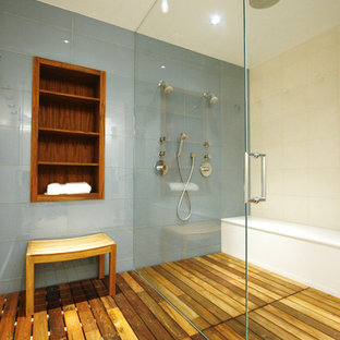 Example of a mid-sized trendy master blue tile and ceramic tile medium tone wood floor walk-in shower design in Chicago with a wall-mount toilet and blue walls