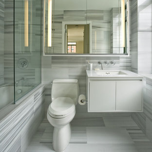 Design ideas for a classic bathroom in New York with a submerged sink, flat-panel cabinets, white cabinets, a submerged bath, a shower/bath combination and grey tiles.
