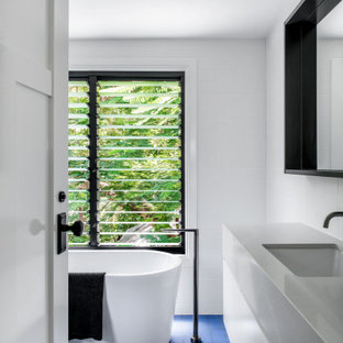 Mid-sized contemporary master bathroom in Brisbane with white cabinets, a freestanding tub, white tile, white walls, solid surface benchtops, blue floor, a single vanity, flat-panel cabinets, porcelain floors, an undermount sink, grey benchtops and a floating vanity.
