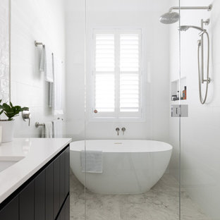 Transitional 3/4 wet room bathroom in Brisbane with raised-panel cabinets, black cabinets, a freestanding tub, white tile, white walls, an undermount sink, engineered quartz benchtops, grey floor, a hinged shower door, white benchtops, a single vanity and a built-in vanity.