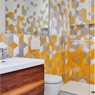 Photo of a contemporary shower room in New York with flat-panel cabinets, medium wood cabinets, a corner shower, a wall mounted toilet, grey tiles, orange tiles, white tiles, a console sink and white floors.