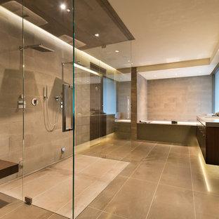 Exemple d'une salle de bain principale tendance avec un placard à porte plane, des portes de placard en bois sombre, une baignoire posée, une douche à l'italienne, un carrelage gris, un carrelage de pierre et un plan de toilette en terrazzo.