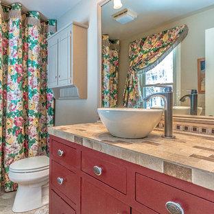 Inredning av ett modernt litet beige beige badrum med dusch, med möbel-liknande, röda skåp, ett platsbyggt badkar, en dusch/badkar-kombination, en toalettstol med separat cisternkåpa, beige kakel, keramikplattor, blå väggar, klinkergolv i keramik, ett fristående handfat, kaklad bänkskiva, beiget golv och dusch med duschdraperi