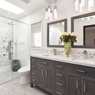 This is an example of a contemporary master bathroom in Calgary with recessed-panel cabinets, a double shower, gray tile, pebble tile, white walls, porcelain floors, marble benchtops and an undermount sink.