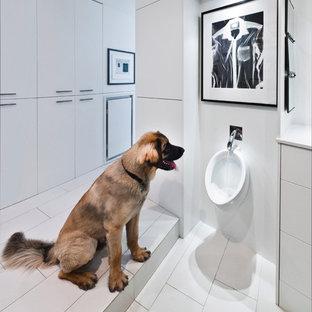 Modelo de cuarto de baño minimalista con puertas de armario blancas, urinario y baldosas y/o azulejos blancos