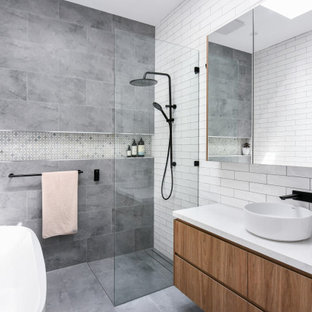 Design ideas for a mid-sized contemporary master bathroom in Sydney with flat-panel cabinets, medium wood cabinets, a freestanding tub, an open shower, a one-piece toilet, white tile, ceramic tile, white walls, ceramic floors, a drop-in sink, engineered quartz benchtops, grey floor, an open shower, white benchtops, a niche, a single vanity and a floating vanity.