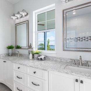 Exempel på ett stort maritimt grå grått en-suite badrum, med skåp i shakerstil, vita skåp, ett fristående badkar, en hörndusch, en toalettstol med separat cisternkåpa, blå väggar, klinkergolv i keramik, ett undermonterad handfat, granitbänkskiva, flerfärgat golv och dusch med gångjärnsdörr