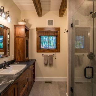 Imagen de cuarto de baño campestre, pequeño, con lavabo encastrado, armarios con paneles empotrados, puertas de armario de madera oscura, ducha abierta, baldosas y/o azulejos grises, baldosas y/o azulejos de piedra, paredes beige, suelo de pizarra y encimera de esteatita