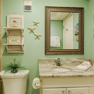 Photo of a small coastal family bathroom in Tampa with raised-panel cabinets, white cabinets, a built-in bath, a two-piece toilet, beige tiles, ceramic tiles, beige walls, ceramic flooring, a submerged sink and granite worktops.