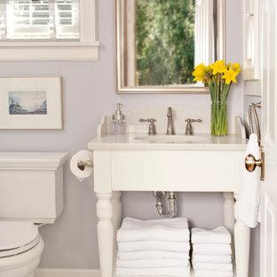 Immagine di una piccola stanza da bagno padronale tradizionale con lavabo sottopiano, ante bianche, top in quarzo composito, WC a due pezzi, pareti viola e pavimento in marmo
