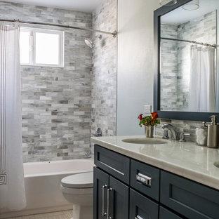 Esempio di una piccola stanza da bagno stile marino con ante in stile shaker, ante blu, vasca ad alcova, vasca/doccia, piastrelle grigie, piastrelle di vetro, pareti grigie, pavimento in gres porcellanato, lavabo sottopiano e top in granito