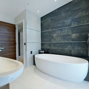 Freestanding bathtub - contemporary gray tile porcelain floor freestanding bathtub idea in Dorset with a wall-mount sink and white walls