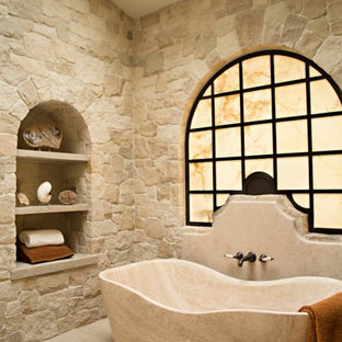 This is an example of a mediterranean master bathroom in Los Angeles with open cabinets and a freestanding tub.