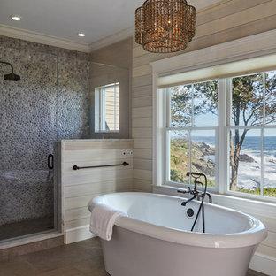 Идея дизайна: главная ванная комната в морском стиле с отдельно стоящей ванной, душем в нише, разноцветной плиткой, галечной плиткой, бежевыми стенами, коричневым полом и душем с распашными дверями