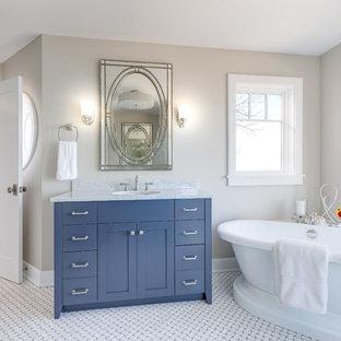 Freestanding bathtub - coastal master freestanding bathtub idea in Chicago with blue cabinets, beige walls and an undermount sink
