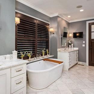 Modelo de cuarto de baño principal, de estilo americano, con puertas de armario blancas, bañera exenta, ducha empotrada, baldosas y/o azulejos grises, paredes grises, lavabo bajoencimera, encimera de granito, suelo amarillo, ducha con puerta con bisagras y encimeras blancas