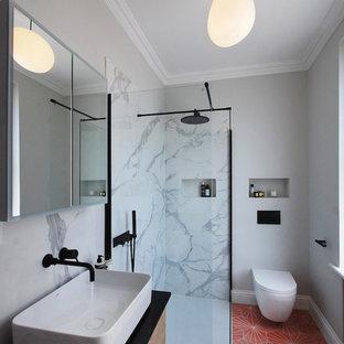 Imagen de cuarto de baño con ducha, moderno, pequeño, con puertas de armario de madera clara, ducha abierta, sanitario de pared, baldosas y/o azulejos de porcelana, paredes grises, suelo de baldosas de terracota, lavabo sobreencimera, encimera de mármol, suelo rosa, ducha abierta, encimeras negras y baldosas y/o azulejos multicolor