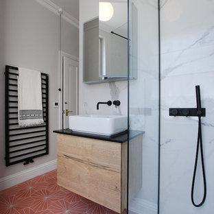 Immagine di una piccola stanza da bagno con doccia minimalista con ante in legno chiaro, doccia aperta, WC sospeso, piastrelle in gres porcellanato, pareti grigie, pavimento in terracotta, lavabo a bacinella, top in marmo, pavimento rosa, doccia aperta, top nero e piastrelle multicolore