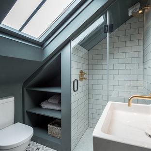 Immagine di una piccola stanza da bagno minimal con doccia aperta, WC monopezzo, pareti grigie, pavimento con piastrelle in ceramica, lavabo sospeso e porta doccia a battente