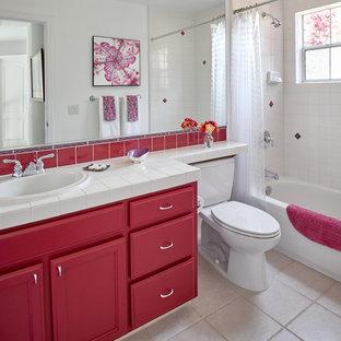 Modelo de cuarto de baño clásico renovado con armarios con paneles empotrados, puertas de armario rojas, bañera empotrada, combinación de ducha y bañera, baldosas y/o azulejos blancos, paredes blancas, lavabo encastrado, encimera de azulejos, suelo beige, ducha con cortina y encimeras blancas