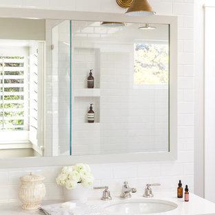 Удачное сочетание для дизайна помещения: большая главная ванная комната в стиле современная классика с фасадами в стиле шейкер, белыми фасадами, белой плиткой, столешницей из кварцита, белой столешницей, угловым душем, бежевыми стенами, полом из фанеры, врезной раковиной, серым полом и душем с распашными дверями - самое интересное для вас