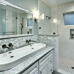 Ejemplo de cuarto de baño infantil, actual, de tamaño medio, con puertas de armario blancas, ducha empotrada, sanitario de una pieza, baldosas y/o azulejos blancos, baldosas y/o azulejos de cerámica, paredes azules, suelo de baldosas de porcelana, lavabo sobreencimera, encimera de cuarzo compacto, suelo blanco, ducha con puerta con bisagras, encimeras turquesas y armarios con paneles empotrados