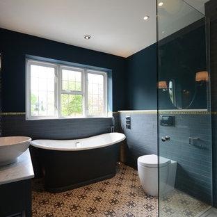 サセックスの中くらいのエクレクティックスタイルのおしゃれな浴室 (シェーカースタイル扉のキャビネット、青いキャビネット、置き型浴槽、オープン型シャワー、一体型トイレ、青いタイル、セラミックタイル、青い壁、セラミックタイルの床、コンソール型シンク、大理石の洗面台) の写真