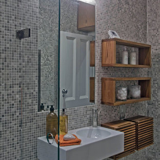 This is an example of a small modern shower room in London with a vessel sink, open cabinets, dark wood cabinets, wooden worktops, a walk-in shower, a wall mounted toilet, grey tiles, mosaic tiles, grey walls and mosaic tile flooring.