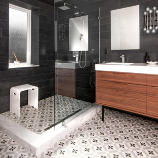 Corner shower - transitional black tile cement tile floor corner shower idea in Toronto with flat-panel cabinets and medium tone wood cabinets