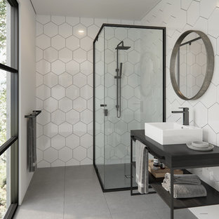 Design ideas for a contemporary 3/4 bathroom in Melbourne with open cabinets, a corner shower, white tile, a vessel sink, grey floor, a hinged shower door and black benchtops.