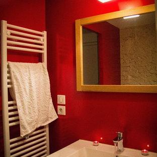 Modelo de cuarto de baño infantil, romántico, pequeño, con armarios con paneles con relieve, puertas de armario marrones, bañera encastrada, sanitario de una pieza, baldosas y/o azulejos con efecto espejo, paredes rojas, suelo de baldosas de cerámica, lavabo de seno grande, encimera de madera y suelo marrón