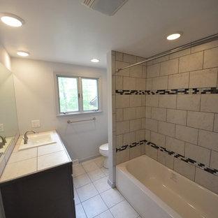 Esempio di una stanza da bagno con doccia tradizionale di medie dimensioni con ante in legno bruno, vasca ad alcova, vasca/doccia, WC a due pezzi, pareti grigie, pavimento in laminato, lavabo da incasso, top piastrellato, pavimento beige, doccia con tenda e top beige