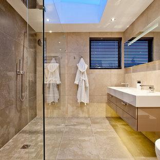 Modernes Badezimmer mit Waschtischkonsole, flächenbündigen Schrankfronten, beigen Schränken und beigefarbenen Fliesen in Surrey