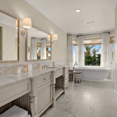 Inspiration for a mid-sized timeless master white tile and marble tile marble floor and white floor bathroom remodel in San Diego with furniture-like cabinets, white cabinets, beige walls, an undermount sink, marble countertops, a hinged shower door, a two-piece toilet and white countertops
