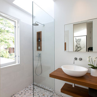 Small contemporary shower room in London with open cabinets, grey tiles, grey walls, a vessel sink, wooden worktops, multi-coloured floors, an open shower, a walk-in shower and pebble tile flooring.