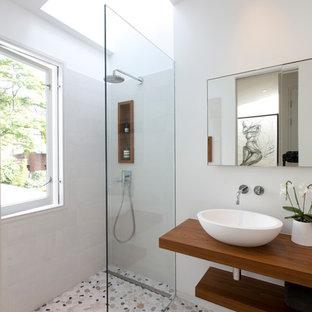 На фото: маленькая ванная комната в современном стиле с открытыми фасадами, серой плиткой, серыми стенами, настольной раковиной, столешницей из дерева, разноцветным полом, открытым душем, коричневой столешницей, открытым душем, полом из галечной плитки и душевой кабиной с