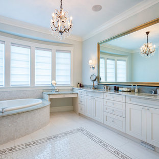 Inspiration for a large master bathroom in Other with beaded inset cabinets, white cabinets, a drop-in tub, a corner shower, white tile, porcelain tile, grey walls, porcelain floors, an undermount sink, granite benchtops, yellow floor, a hinged shower door and grey benchtops.
