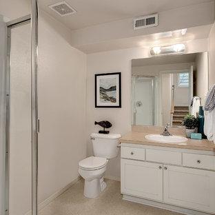 Exempel på ett litet klassiskt badrum med dusch, med skåp i shakerstil, vita skåp, en toalettstol med separat cisternkåpa, beige kakel, gula väggar, linoleumgolv, ett nedsänkt handfat och bänkskiva i akrylsten